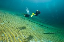 Divers in the sunny and crystal clear Austrian Sameranger Lake